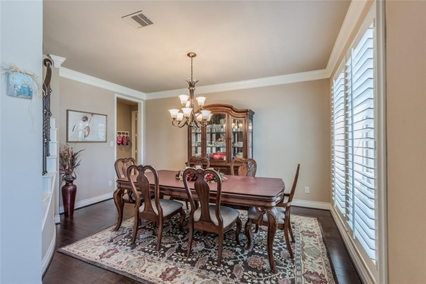 Upgraded crown moldings and wood flooring add special touches to this elegant formal dining room. Large windows with custom shutters overlook the front lawn. (photo 5)