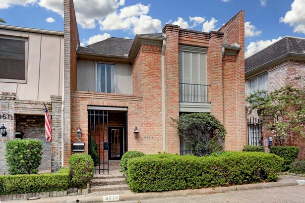 Beautifully maintained, red brick traditional townhome in the Woodlake Forest neighborhood. Note the wrought iron gate at the entry. (photo 1)