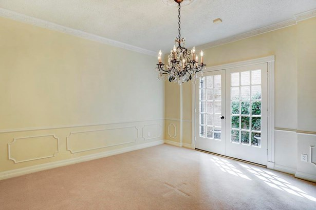 Dining room with French doors leading to entry courtyard. Decorative trim detail and crown molding. (photo 4)