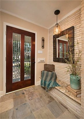 This lovely leaded glass insert mahogany front door welcomes you to this beautifully redone home done in neutral color palette throughout. In the entry, there are slate tile flooring and this very cool interior brick accent wall. (photo 4)
