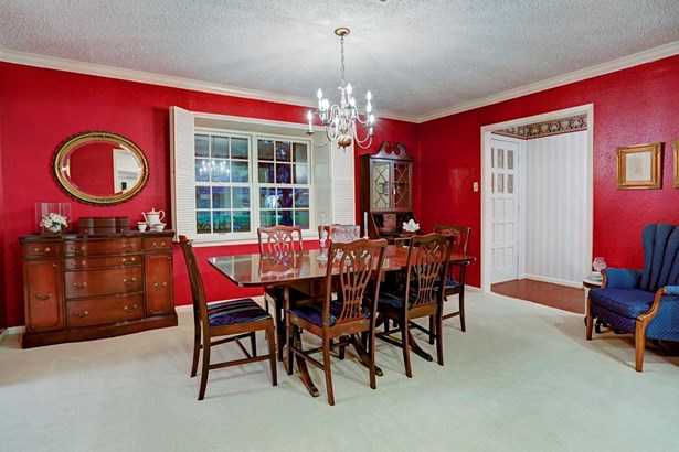 An elegant dining room, graced with a traditional brass chandelier and shutters, lines the front of the home with grand views to the lush front yard. (photo 4)