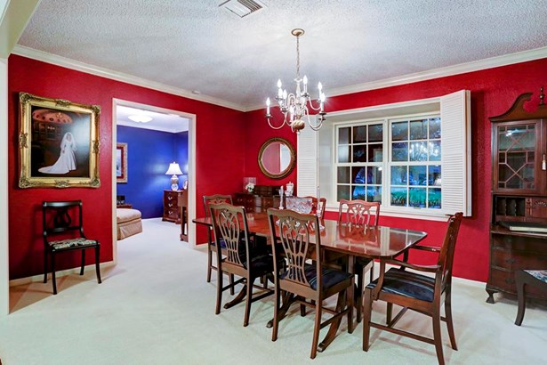 This central room is currently used as a formal dining room (easily re-purposed as a living room). With grand openings, the room pours into so much of the house: entry way, sitting room, and living room. Notice the blue formal sitting room beyond. (photo 5)