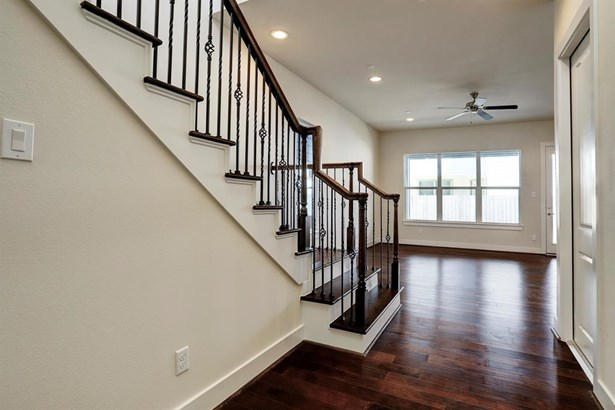 Upon entrance, you are welcomes to the open concept floor-plan with a 2 story foyer, living area with seamless flow to dining and kitchen all overlooking the privately fenced covered patio and backyard. Handsome hardwoods throughout the entire level. Door (photo 4)