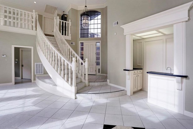 Inviting two story entrance features an elegang floating staircase, wet bar and tile floors. (photo 3)