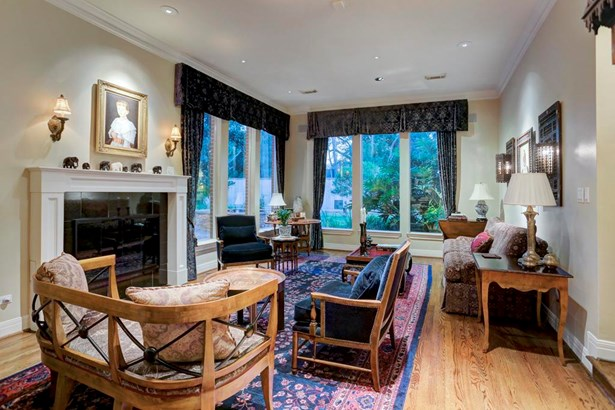 Spacious formal living room with oak hardwoods, gas fireplace, floor to ceiling windows overlooking water feature and grounds (photo 4)