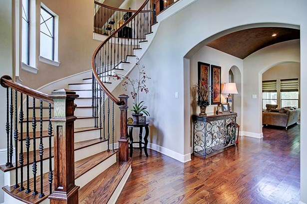 A spiral staircase compliments the two story entry and open floor plan. (photo 4)