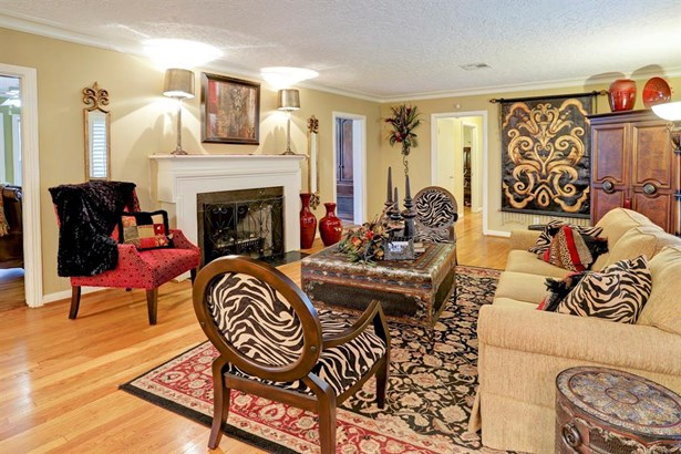 The formal living room to the right of the entry includes lovely hardwood flooring, a fireplace with gas logs, and ample space for relaxing or entertaining. (photo 4)