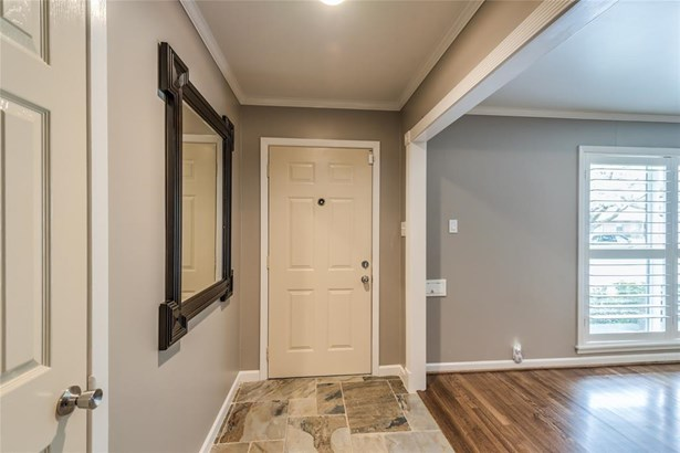 Slate entry area with crown molding accents opens to the living room on the right. (photo 4)