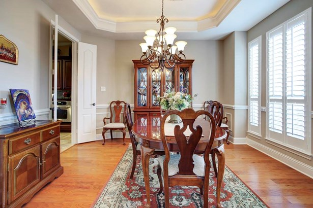 To the right of the entry is the formal dining room with chandelier, wood flooring, cove lighting and plantation shutters. (photo 4)