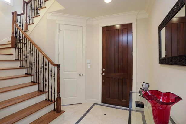 Entry vestibule with stone flooring, access to garage and first floor bedroom and bathroom. Hardwood floor staircase leads to living areas. (photo 3)
