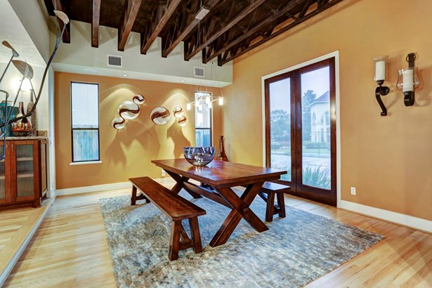 Dining area featuring exposed truss ceiling system and tons of natural light. (photo 4)