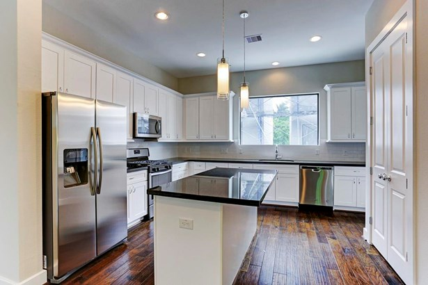 Bight open island kitchen with stainless steel appliances. (photo 3)