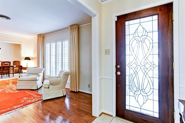 The front door is mahogany with leaded glass decorative insert to allow extra light to stream into the entry hall. Upon entering, one notices fine touches like a marble tile foyer floored entry, crown and chair rail moldings, and entering then directly in (photo 4)