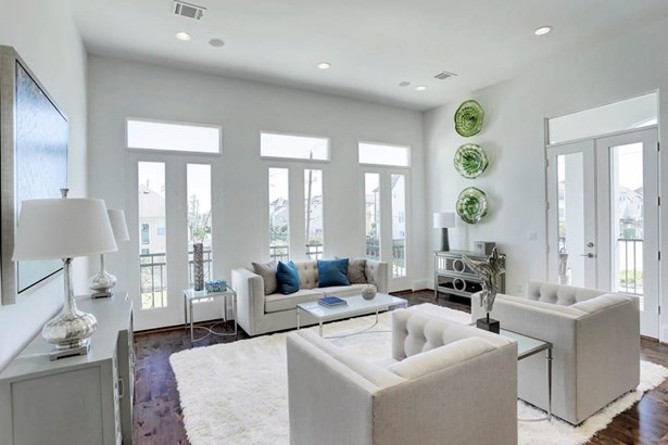 Another view of the living room in order to see all of the windows! The French doors lead to a large 2nd floor balcony equipped with a gas line for your outdoor kitchen. (photo 4)