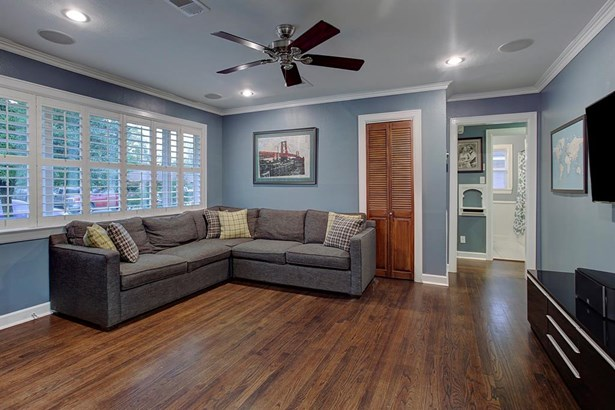 Large living room over looks the front yard through a wide double paned window. Original hardwood floors have been refinished in a neutral warm brown tone. (photo 5)