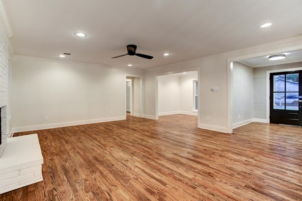 Wide entry is dressed with grass cloth wall paper, sleek flush mount with black and gold accents, divided light front door with Baldwin hardware and wood flooring. Cased opening leads into the large living room with gas fireplace. Recessed lighting and sl (photo 5)