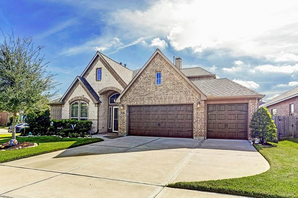 The exterior is composed in neutral brick and stone. The lush green landscaping and trees are easy to maintain and welcome you as you approach the front door. There is a sprinkler system that covers the front, back and side yard of the home. (photo 2)