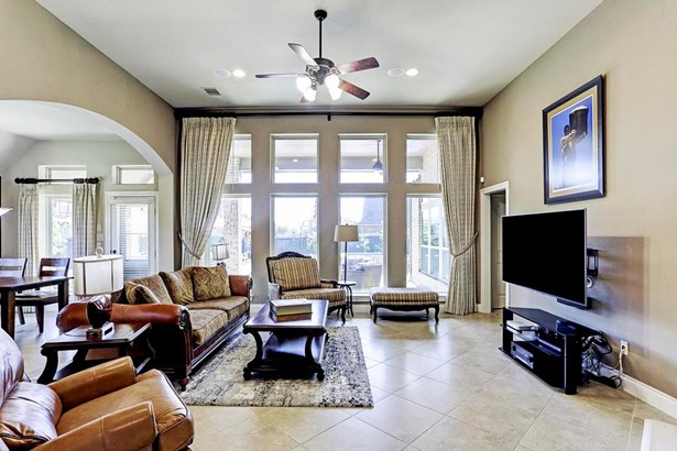 Alternate view of the living room showing the open concept layout. Tile flooring allows for easy maintenance. The abundance of windows flood the home with natural light. (photo 5)