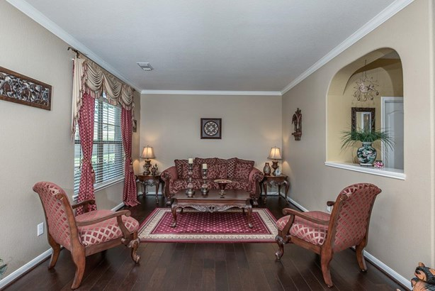 This formal living room has gorgeous wood floors, crown molding, large double window and pass-through opening for a more open feel. (photo 4)