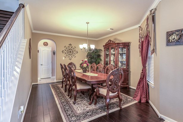 The formal dining room also has wood floors & crown molding with center dining light fixture and window to the front lawn. (photo 5)
