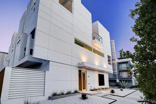 Front facade featuring white pebble gardens and subtle yet sleek design (photo 3)