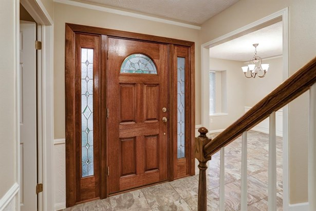 Front entry hall with high end tile floors with a mixture of earth tones and grays is open to formal dining room. (photo 3)