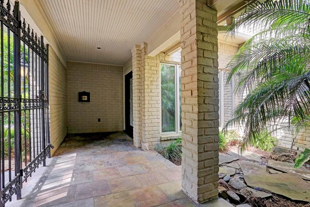 Coming off of the front circle drive, one enters into a lockable, gated courtyard with slate pavers and a warm and welcoming atrium garden area. (photo 4)
