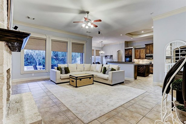 Tile floor is and soothing paint colors are carried into living room. Room features gas log fireplace and built in cabinets with shelving for storage and display. Cased windows let in light and provide view of pool and lushly landscaped backyard. (photo 5)