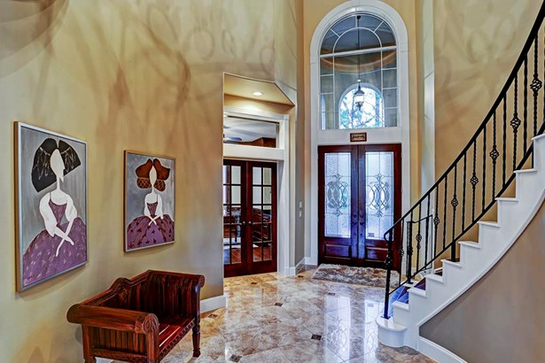 Upon entrance the elongated spiral staircase, immaculate travertine tiling and high ceilings are highlighted. (photo 3)