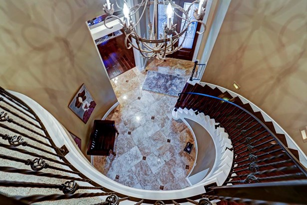 The spiral staircase connected to the foyer is one of two ways to access the upstairs. (photo 4)