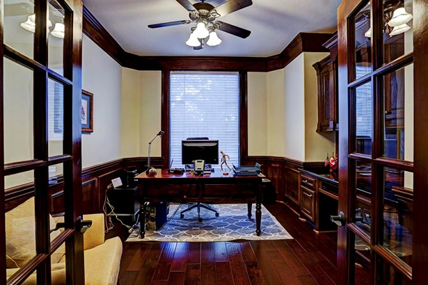 Rich wood floors and wood finish liven up the enclosed office space found beyond the French doors. (photo 5)
