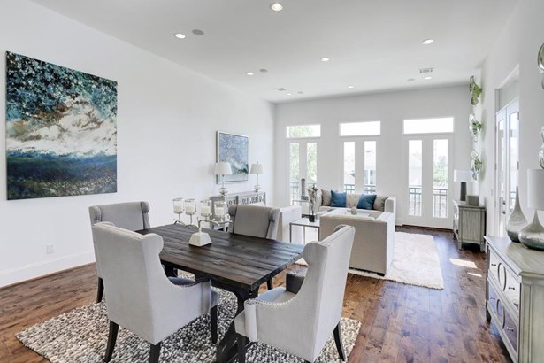 As you enter the 2nd floor, your welcomed by 12 foot soaring ceilings and a very large, open room. You have plenty of space for a much longer dining room table that what is shown here. (photo 3)