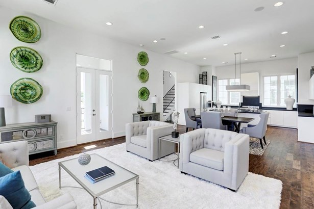"""Here is the view from the living area back toward the dining and kitchen. You have plenty of recessed lighting, not to mention a vast amount of natural light from the """"Romeo and Juliet"""" with transom style windows and balcony on this second floor. (photo 4)"""