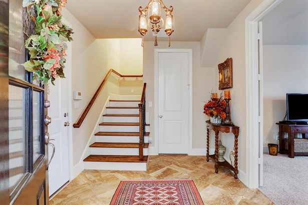 Entry foyer has travertine floor laid on diagonal and coat closet. Chandelier is excluded from sale. (photo 3)