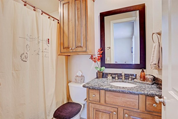 The bathroom off of the 2nd bedroom has granite counter, custom cabinets, and tub/shower combo with tile surround. (photo 5)