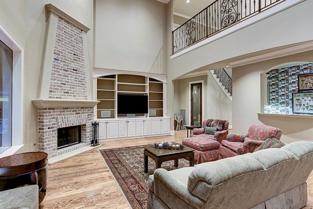 The family room features an impressive double vaulted ceiling, gas fireplace, built-in bookshelves and hardwood floors. Note the full service bar to the right and wine grotto to the upper left. (photo 5)