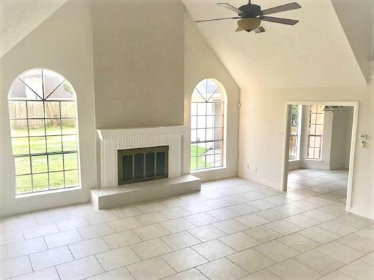 The 17x19 SF living room has tile floor, fireplace with gas connections, high ceiling, and ceiling fan with light kit. (photo 5)