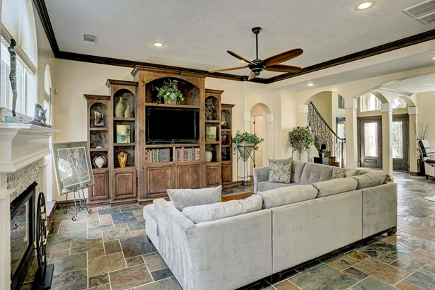 Such a gorgeous family room with slate floors, great built in, and cozy fireplace. (photo 2)