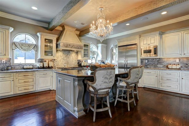The perimeter cabinets are antiqued while the island is painted in a high gloss. The perimeter counter tops are grey quartzite and the island is a leathered black granite. There are built in spice racks and some of the cabinets have glass fronts. (photo 4)