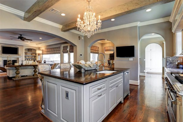 This chef's kitchen boasts distressed beams, a crystal chandelier, Viking appliances, and an industrial sink faucet. (photo 5)