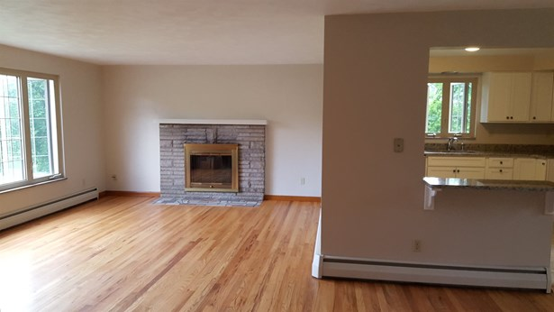 Living room with triple windows for natural light and woodburning fireplace. (photo 4)