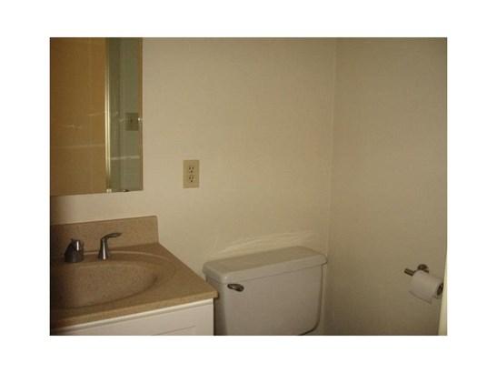 First floor half bath with corian counter top on vanity and ceramic tile floor. (photo 5)