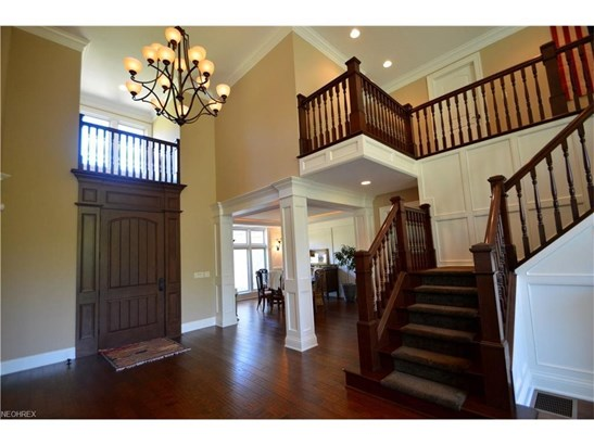 Entry foyer architectural detail includes decorative columns, crown molding, wainscot & open staircase (photo 4)