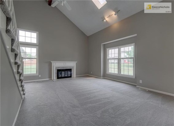 Large living room with updated tile around fireplace.  New carpet, paint and ceiling fan. (photo 5)