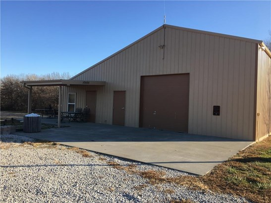 Recently renovated building includes large shop and one bedroom apartment.  Check out the covered patio, sun patio, fire pit, pond, dock, large concrete apron at entrance, tall shop door for large vehicles, and lots more! (photo 2)
