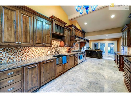 The kitchen has been completely updated with Knotty Beech cabinets and is thoughtfully appointed in every aspect.  This view showcases the custom tile backsplash and you can see the granite farm sink which offers full size dishwashers on BOTH sides of the (photo 4)