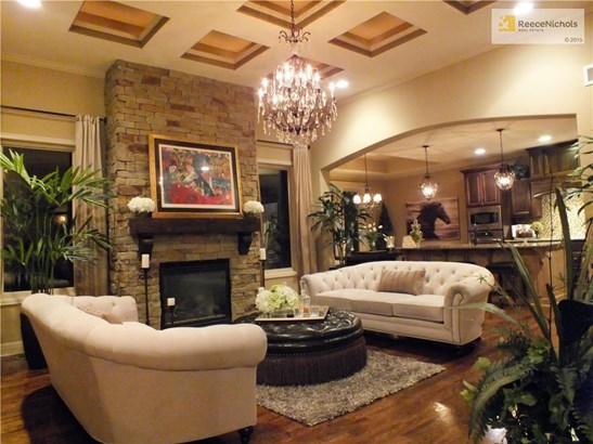 Elegant Great Room with stone fireplace, chandelier and decorative ceiling. (photo 1)