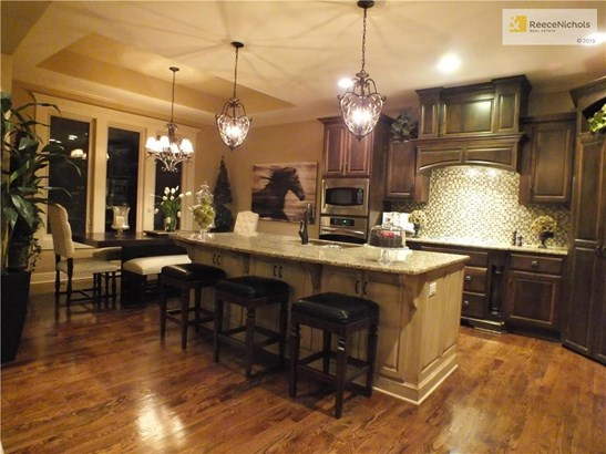Upgraded kitchen with stainless appliances, granite island and custom wood covering over hood. (photo 2)