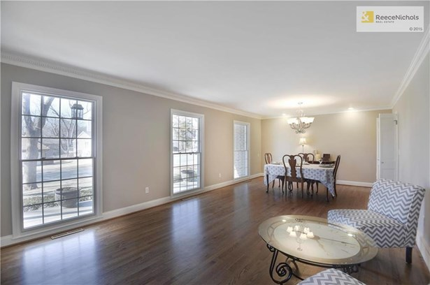 The HUGE Living Room/Dining Room combo spans along the front of the house and offers three large Pella windows to let the natural light shine in.  These floors were just refinished & beautiful.  Smooth ceilings, gorgeous crown molding and fresh paint. (photo 4)