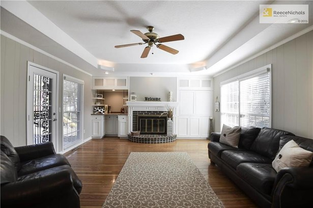 Charming Family Room is freshly painted and boasts hardwood floors and one of two access points to the backyard and patio.  Built-ins on both sides of the brick fireplace great for storage. (photo 5)